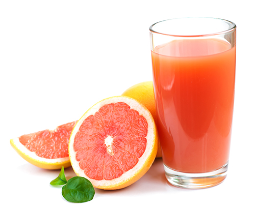Grapefruit juice and ripe grapefruits on a white background